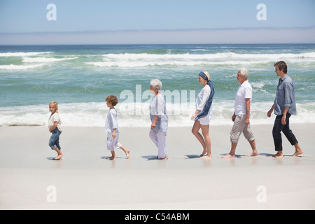 Family at beach walking in row with kids - Stock Photo