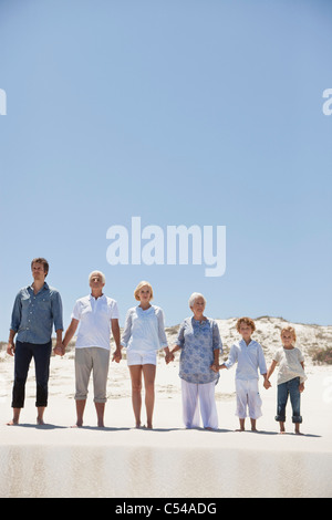 Family standing on the beach - Stock Photo