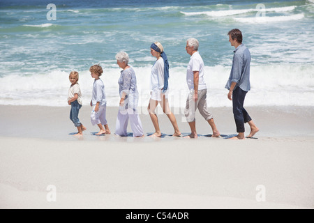 Family walking in row with kids at beach - Stock Photo