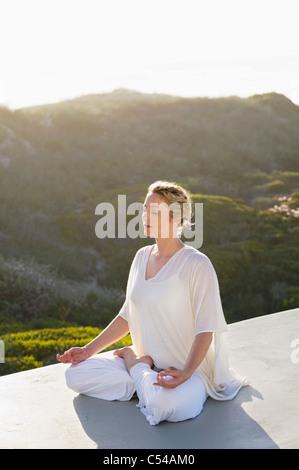 Mid adult woman meditating - Stock Photo