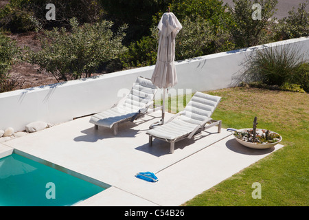 High angle view of lounge chairs at poolside - Stock Photo