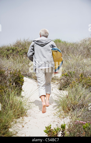 Rear view of a senior man carrying surfboard on the beach - Stock Photo