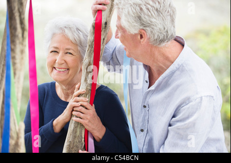 Senior couple standing near a tree decorated with ribbons - Stock Photo