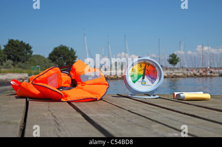 High sun UV index reading on a portable UV index meter on a July afternoon. Recommended sunscreen at hand as is - Stock Photo