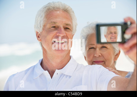Happy senior couple taking a picture of themselves with a digital camera - Stock Photo