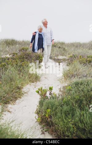 Senior couple walking on the beach - Stock Photo