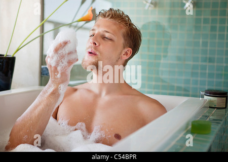 Man having bubble bath in a bathtub - Stock Photo
