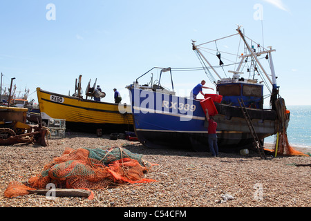 Traditional fishing boats unloading catch of fish on Hastings beach East Sussex England UK GB - Stock Photo