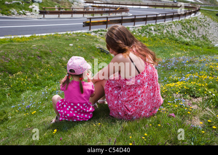 18 and 3 years old girls sitting in Pennine Alps, Valais Alps from Great St Bernard Pass - Stock Photo