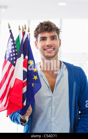 Portrait of a man holding flags of various countries at an airport - Stock Photo