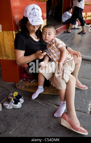 Chinese woman / lady tourist with her sleeping son / boy / tired child. The Forbidden City, Beijing, China. - Stock Photo