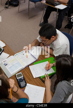 Students work together in group using textbook paper and calculator in classroom at Mission Early College High School - Stock Photo