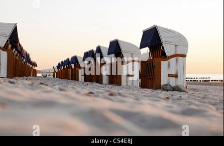 Roofed wicker beach chairs, beach, Baltic Sea, sunset, seaside resort of Ostseeheilbad Heiligendamm, Germany - Stock Photo