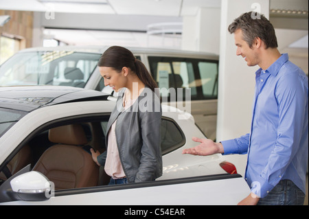 Young woman checking car from inside while man holding the door - Stock Photo