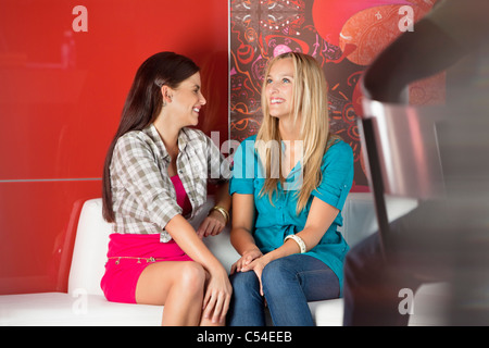Female friends sitting on a sofa in a cafe - Stock Photo