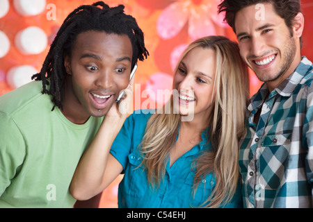 Friends talking on a mobile phone in a bar - Stock Photo