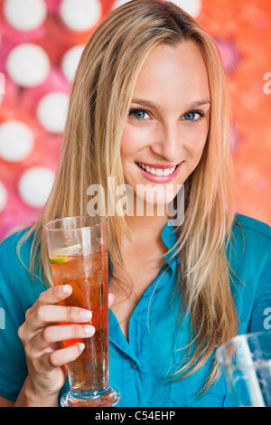 Portrait of a beautiful woman having ice tea in a bar and smiling - Stock Photo