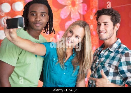 Friends taking a picture of themselves with a mobile phone - Stock Photo