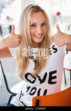 Portrait of a beautiful woman showing thumbs up at a cafe - Stock Photo