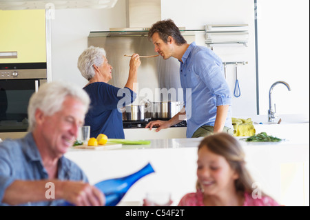 Man pouring water into a glass while his wife feeding food to her son - Stock Photo