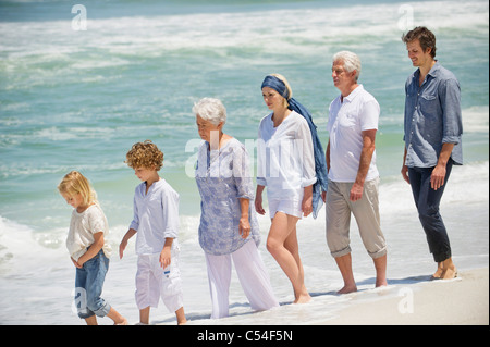 Multi generation family walking in a line on the beach - Stock Photo