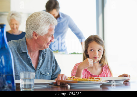 Girl eating food at a dining table with her grandfather sitting near her - Stock Photo