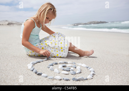 Girl arranging pebbles in spiral shape on the beach - Stock Photo
