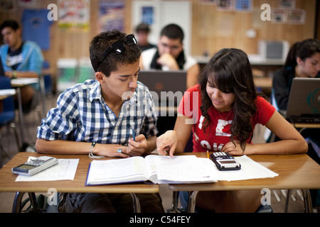 Male and female Hispanic students laugh together in math class at Mission Early College High School in El Paso TX - Stock Photo