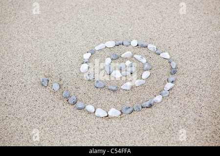 Pebbles arranged in spiral shape on beach - Stock Photo