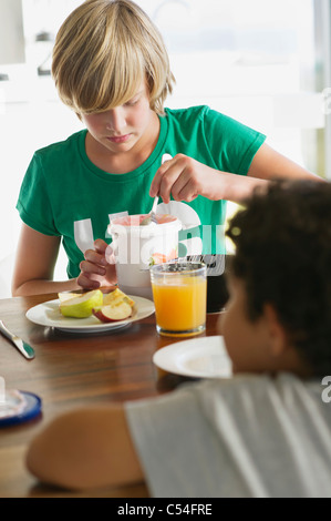 Teenage boy having breakfast with his brother sitting in front of him - Stock Photo