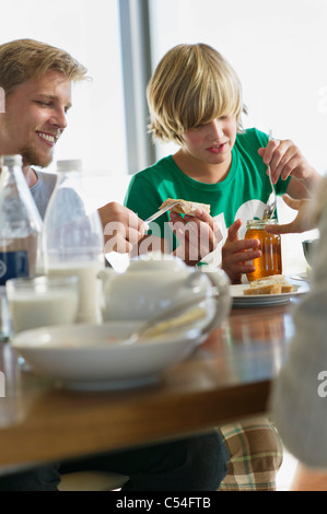 Teenage boy having breakfast with his parents - Stock Photo