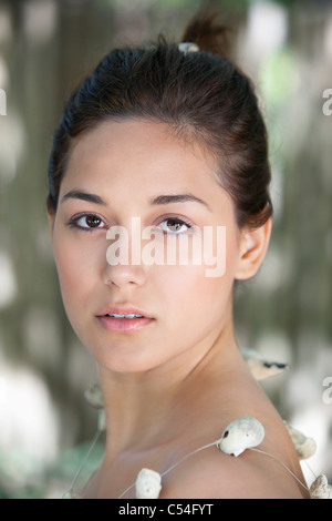 Portrait of a beautiful young woman wearing shell's necklace - Stock Photo
