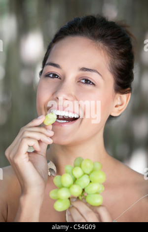 Portrait of a young woman eating grapes - Stock Photo
