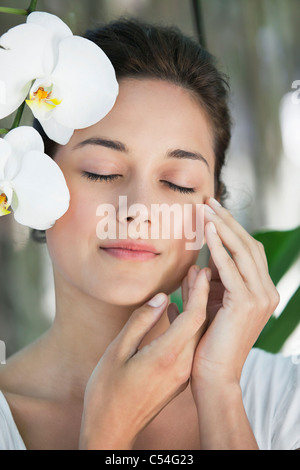Beautiful young woman standing by the flower with her eyes closed - Stock Photo