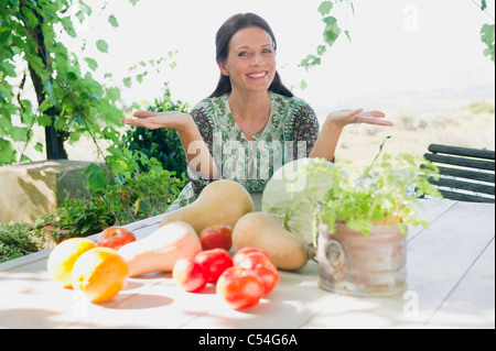 Portrait of a mature woman sitting with vegetables on table - Stock Photo