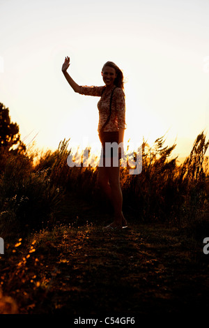 Smiling woman waving hand and smiling - Stock Photo