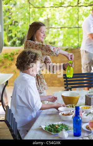Smiling siblings arranging food at dining table with father in the background - Stock Photo