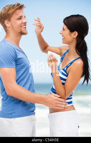 Woman applying suntan lotion on man's face - Stock Photo