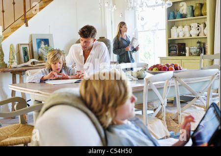 Man teaching little boy while family members busy doing their work at house - Stock Photo