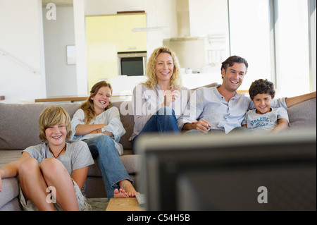 Family watching TV together at home - Stock Photo