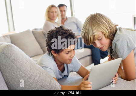 Brothers using a digital tablet with their parents looking at them - Stock Photo