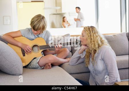 Teenage boy playing a guitar and his mother listening - Stock Photo