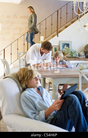 Man talking to little boy with brother using digital tablet in foreground at house - Stock Photo