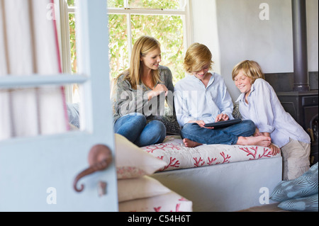 Children and their mother using digital tablet at house - Stock Photo