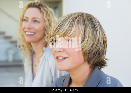 Close-up of a teenage boy smiling with his mother - Stock Photo