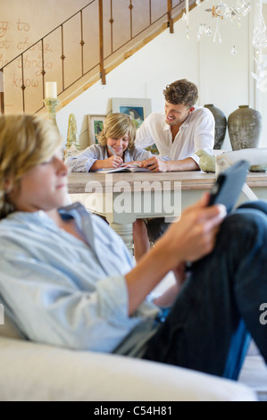 Man teaching little boy with brother using digital tablet in foreground at house - Stock Photo