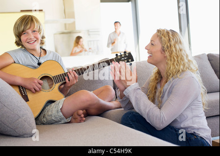 Teenage boy playing a guitar with his mother clapping - Stock Photo