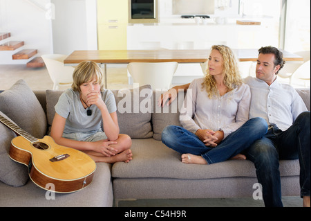 Couple looking at their son looking sad - Stock Photo