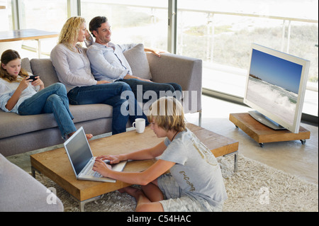 Couple watching television set while their children busy in different activities - Stock Photo