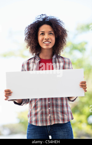 Woman holding a blank placard - Stock Photo